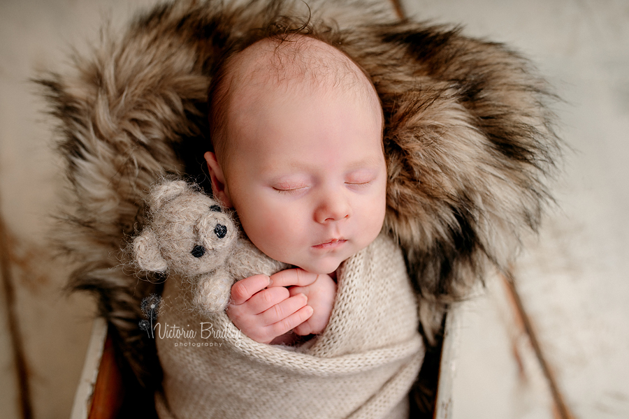 baby newborn boy holding small teddy