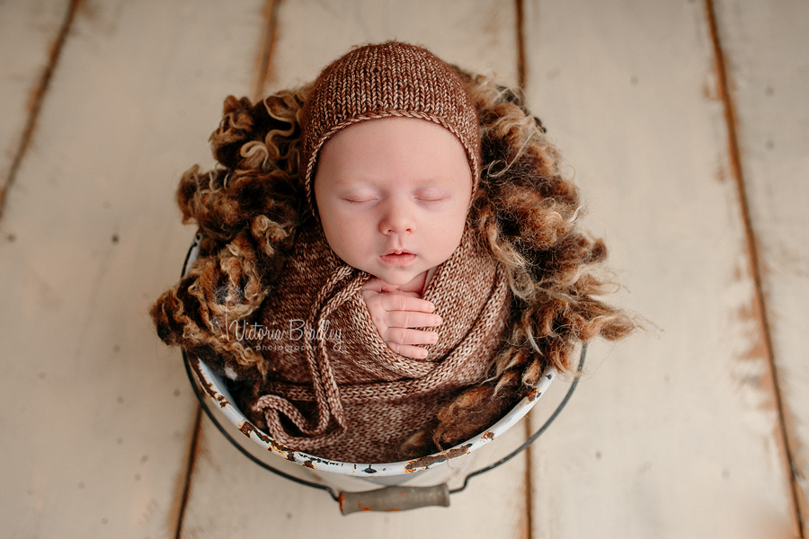 newborn baby boy in brown flecked wrapped and bonnet in white bucket with brown curly fur layer