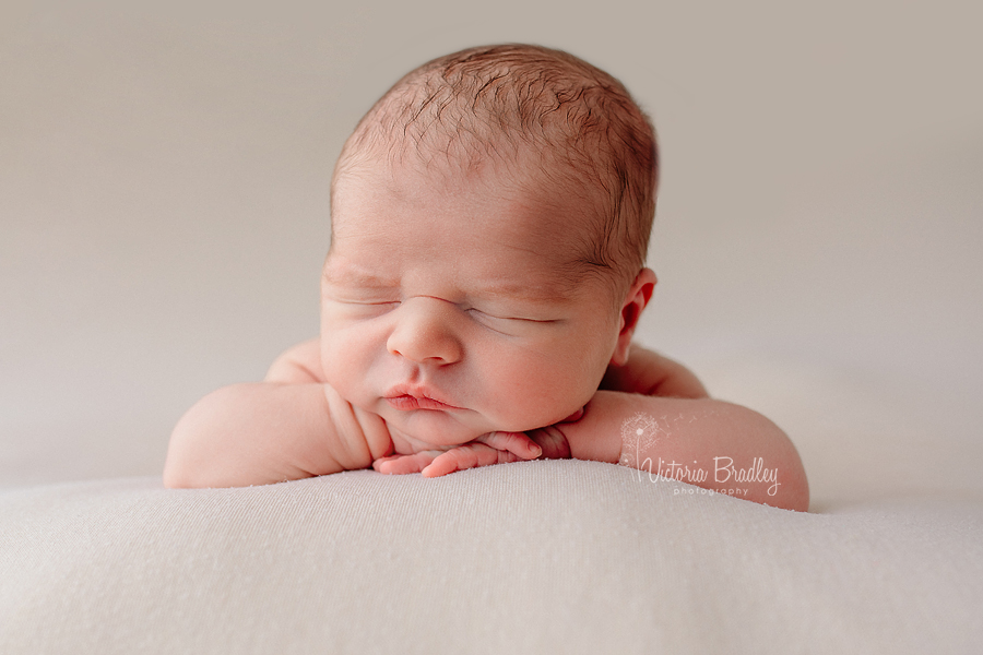 chin on hands pose baby newborn photo on cream backdrop