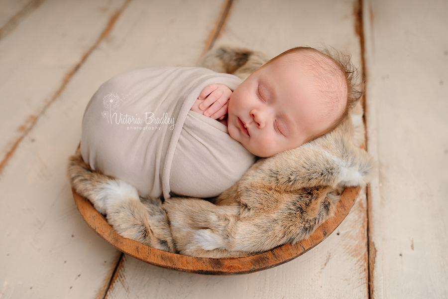 newborn baby boy wrapped on fur in wooden bowl