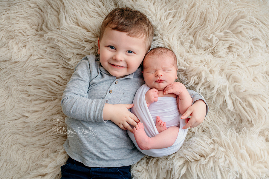 newborn and sibling image from newborn photography session on cream flokati