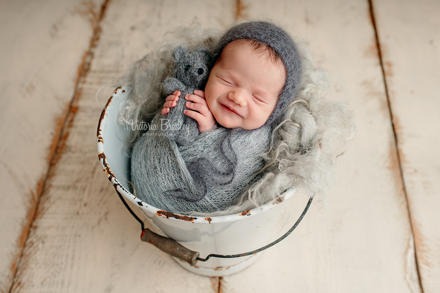 wrapped newborn baby girl newborn photography in grey wrap with grey teddy in white bucket on cream floor boards