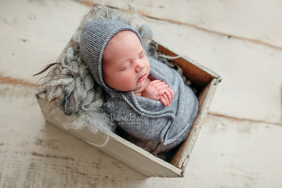 baby wrapped in crate in grey