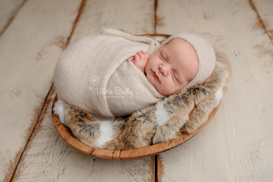 wrapped newborn baby boy in cream