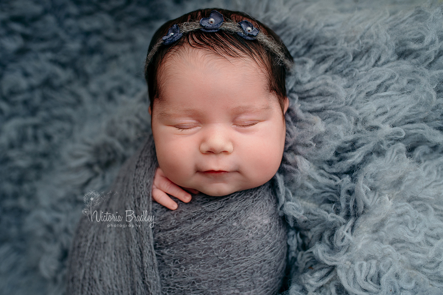 smiling newborn baby girl wrapped in grey