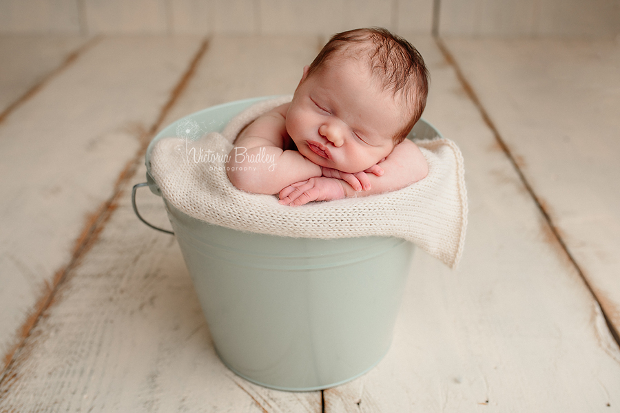 chin on hand pose newborn baby girl in mint bucket