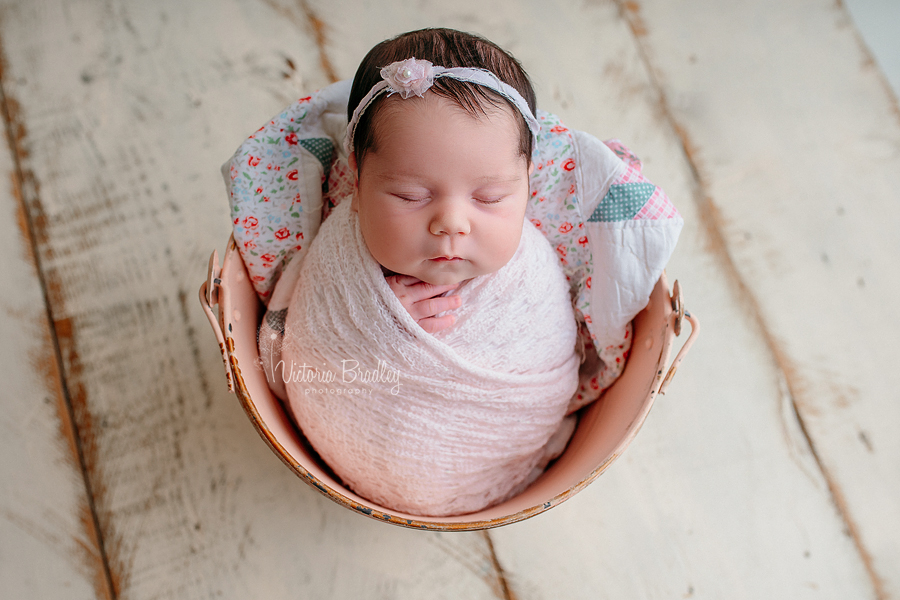 wrapped baby girl newborn in a pink bucket wrapped in a pink knit wrap