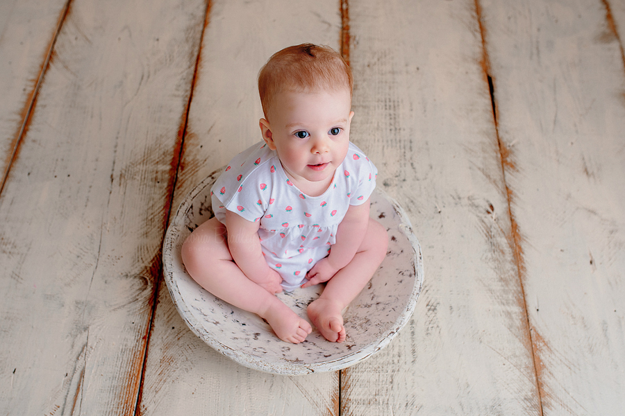 baby girl sat in a white wooden bowl
