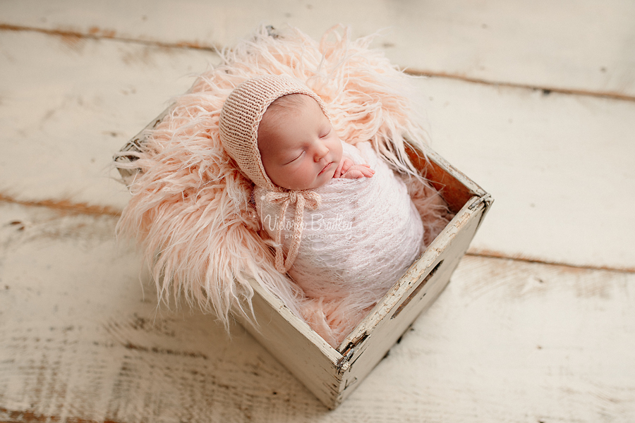 wrapped newborn in crate, pale pinks