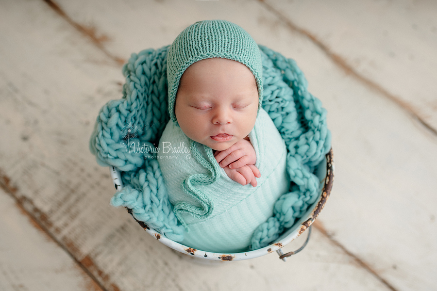 wrapped newborn with mint stuffer and wrap, white bucket