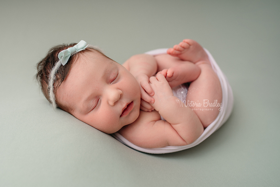 wrapped newborn on sage green