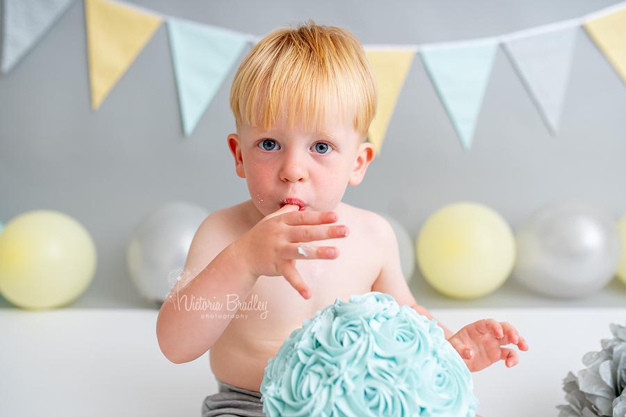 2 year old boy cake smash eating cake