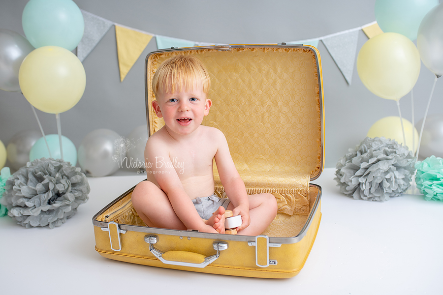 2 year old boy sat in a yellow suitcase