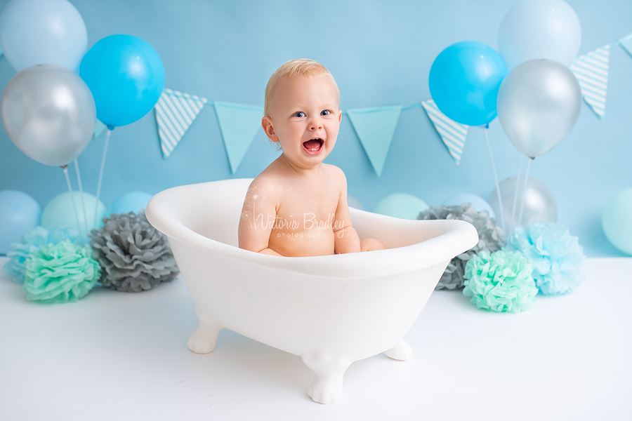 Baby boy in white bath tub for cake smash