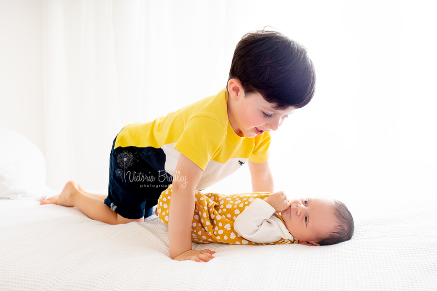 sibling and newborn photography on white.