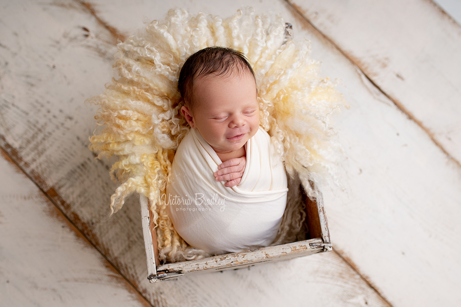 wrapped smiling newborn pastels yellows