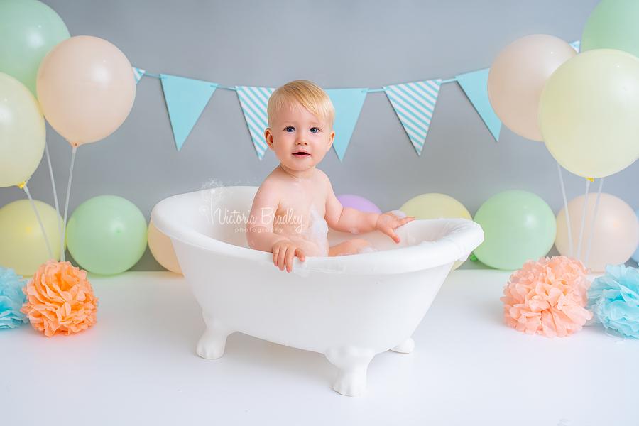 baby boy cake smash rainbow in white bath tub