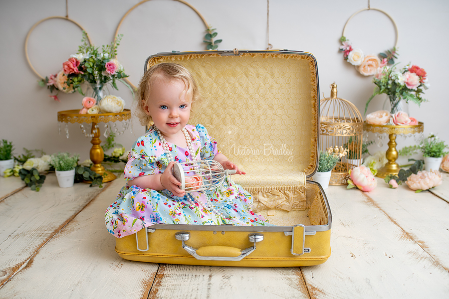 baby girl in yellow suit case