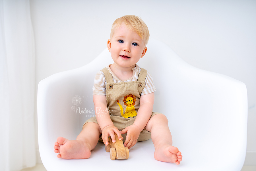 1 year old sat on white chair