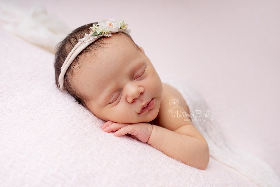 sleepy newborn on pink blanket