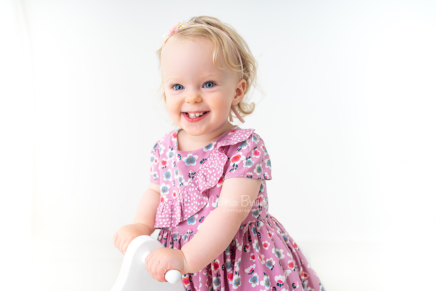 baby girl in floral dress on white rocking horse close up