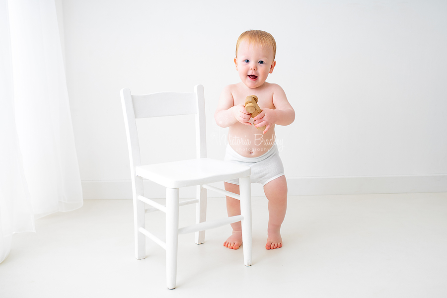 baby with wooden car next to white chair