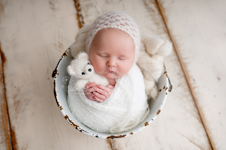 wrapped newborn in white bucket