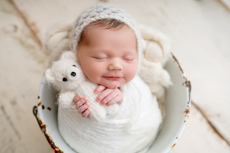 wrapped baby holding mini teddy