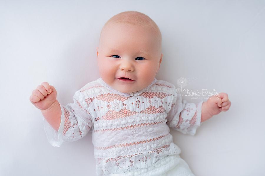smiley newborn on white backdrop