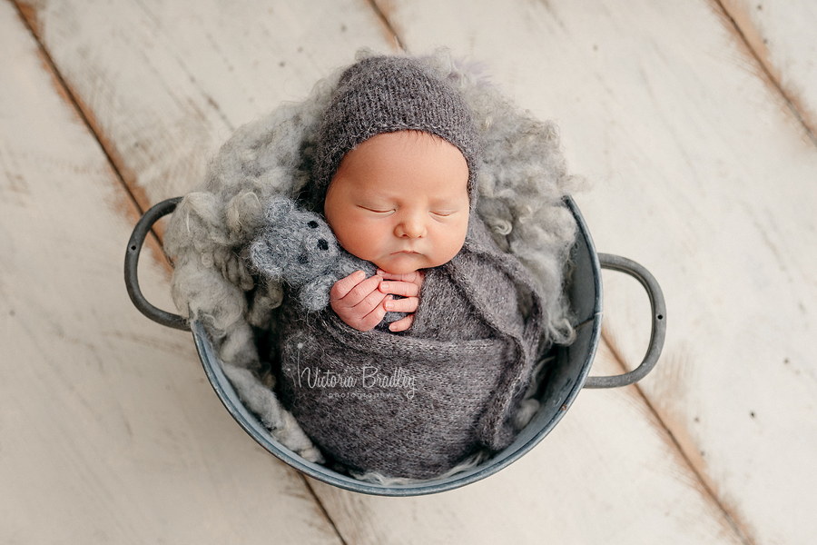 wrapped newborn in grey bucket
