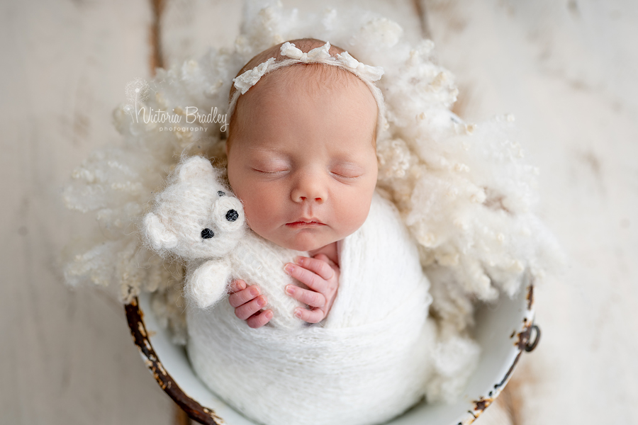 baby girl holding teddy