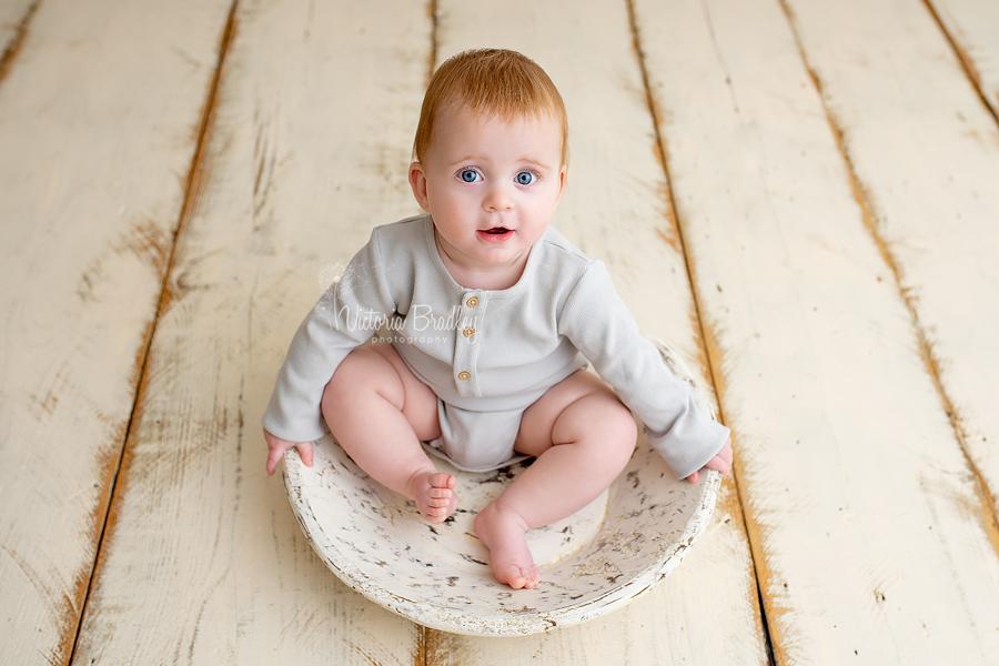 sitter baby in wooden bowl