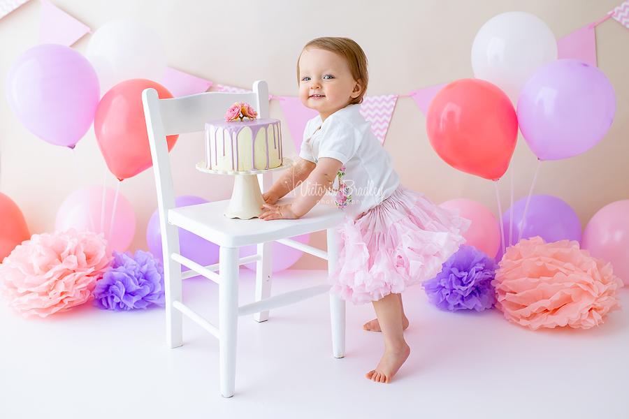 pink and purple baby girl cake smash