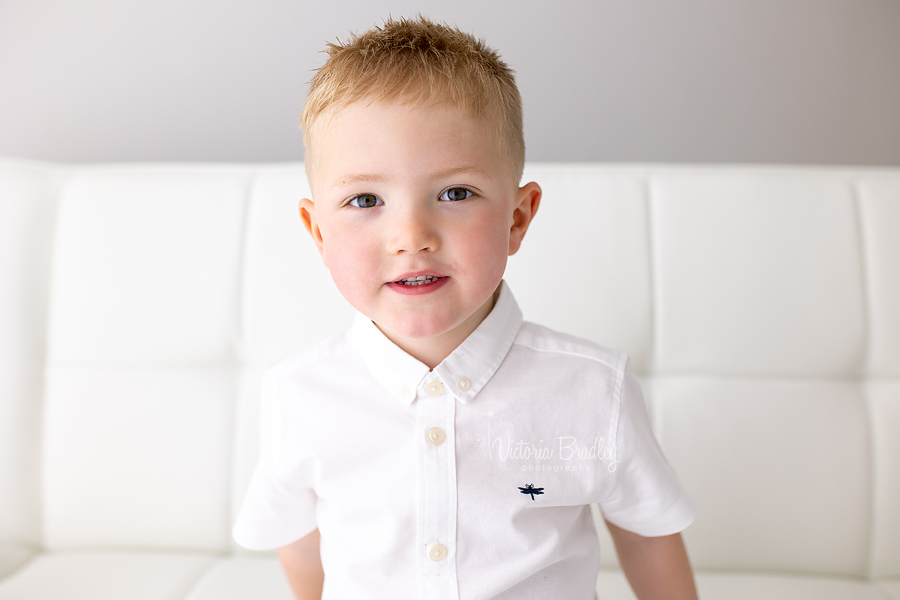 sibling photography, boy on white sofa