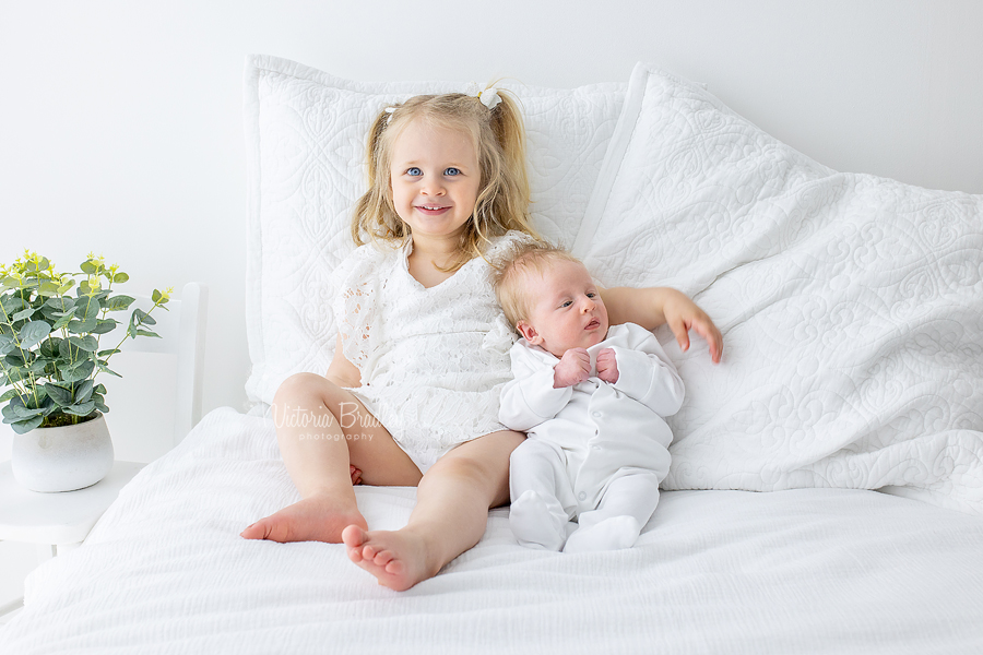 sibling and newborn on white room set