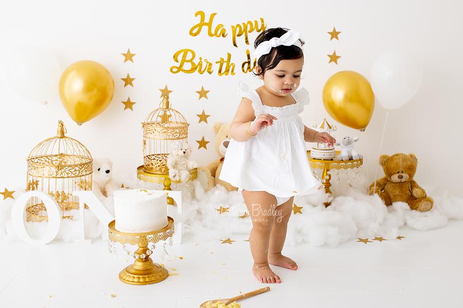 gold and white baby girl cake smash