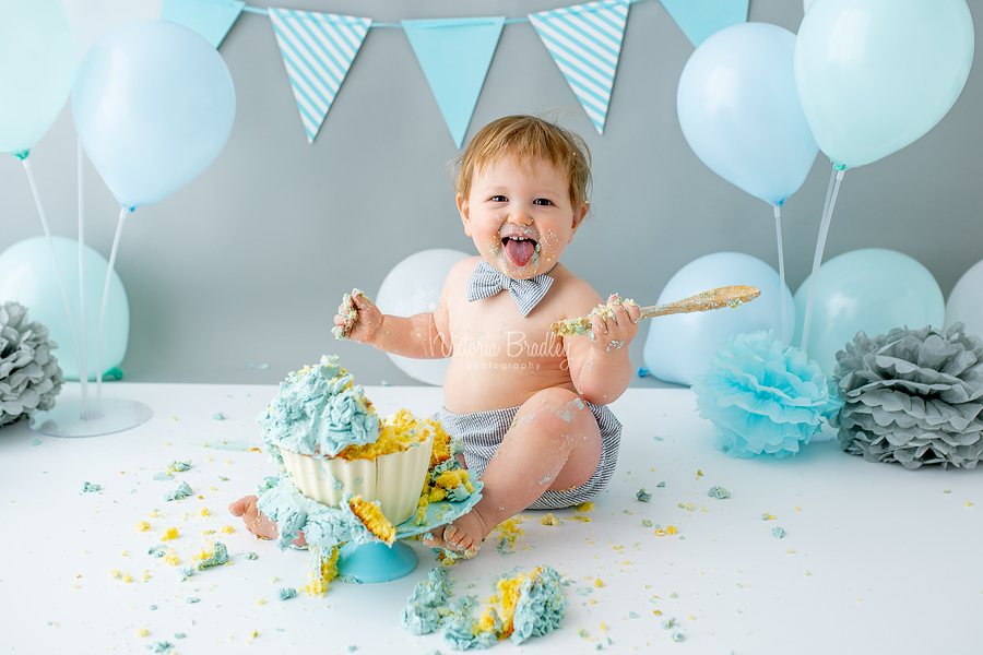 smiling baby boy cake smash with spoon