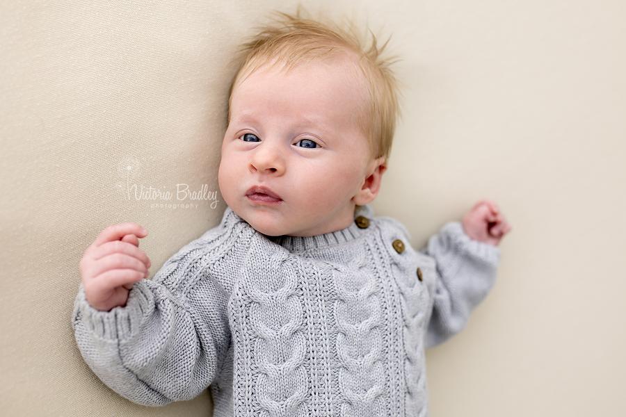 awake newborn boy in grey romper
