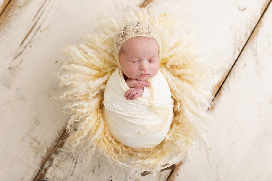 wrapped newborn on pale yellow