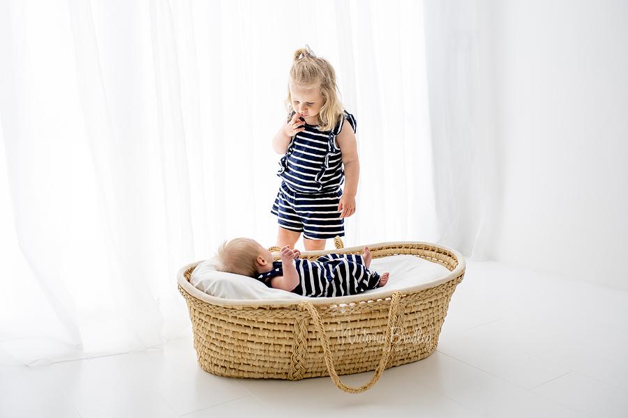 sibling and newborn Moses basket
