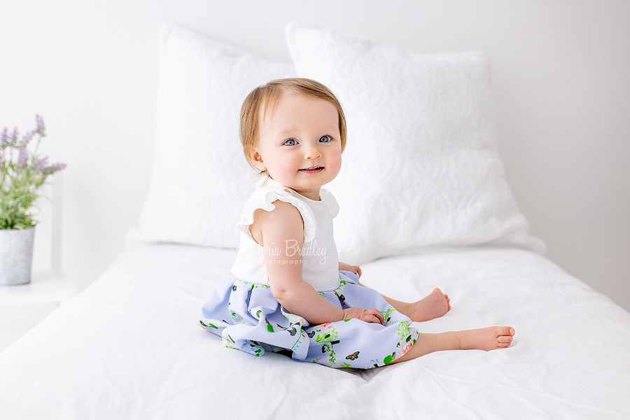 baby girl on white bed set up with lavender