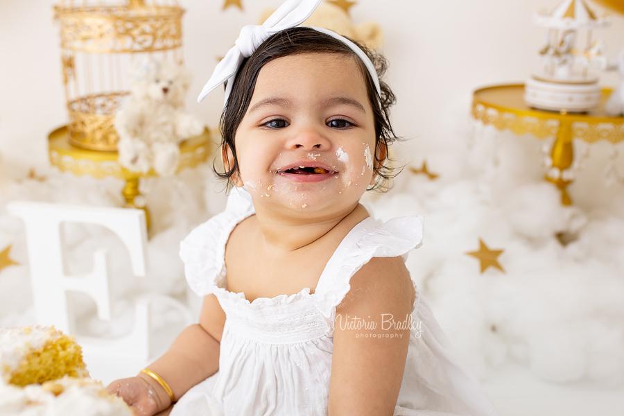 smiling baby girl cake smash gold and white
