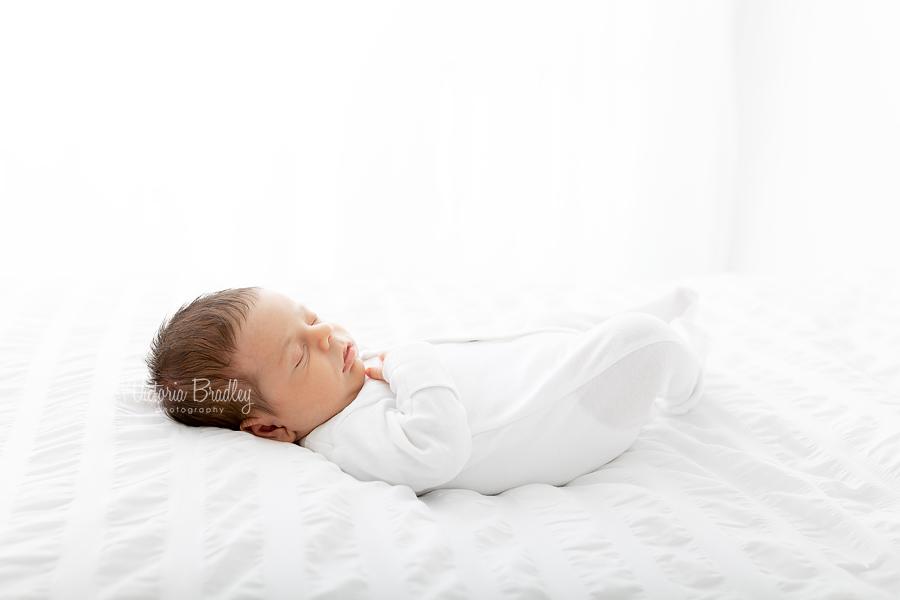 newborn on white bed