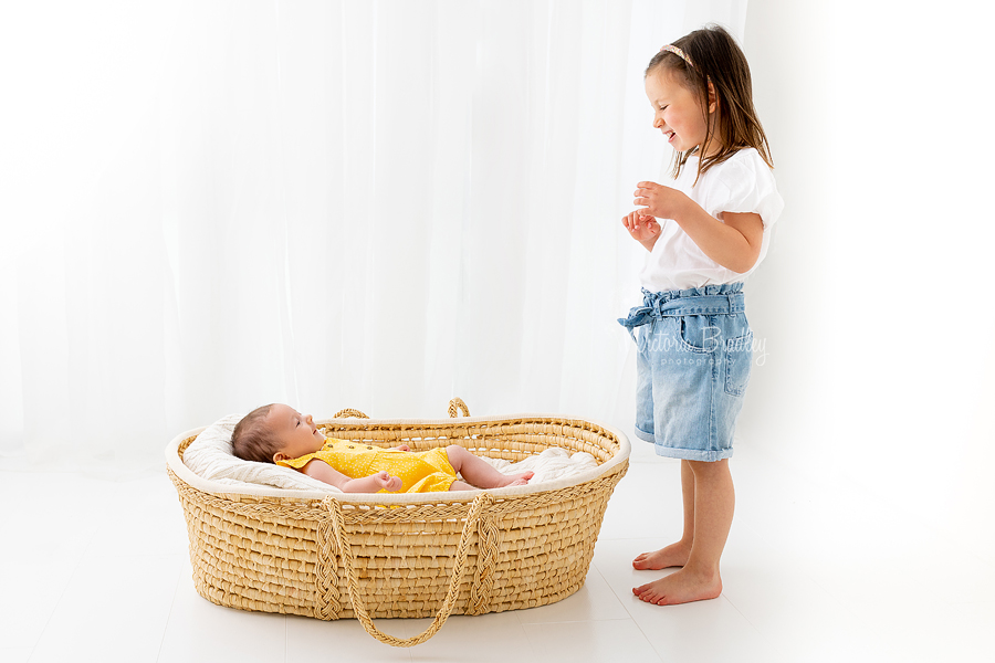 4 year old and newborn in Moses basket