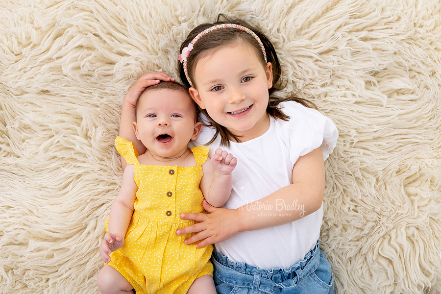 11 week old and 4 year old sibling photography on flokati rug