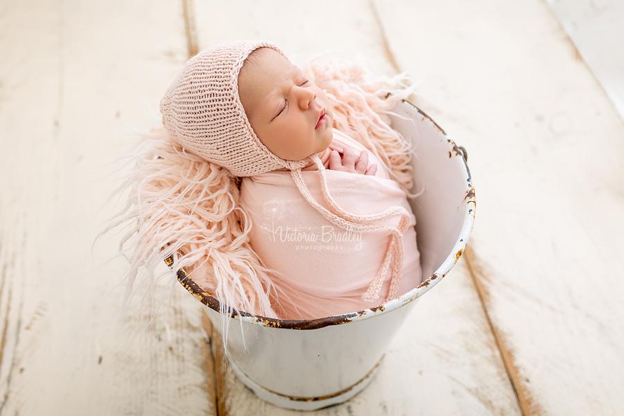 wrapped newborn in peach in white bucket