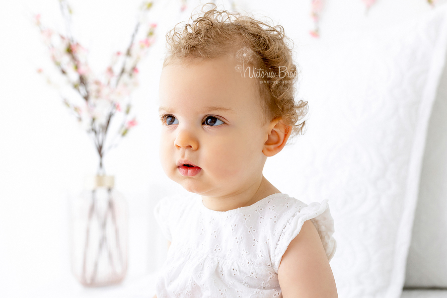 close up of baby on white with blossom