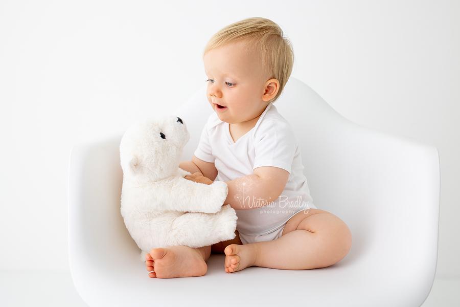 baby boy in white with white polar bear toy