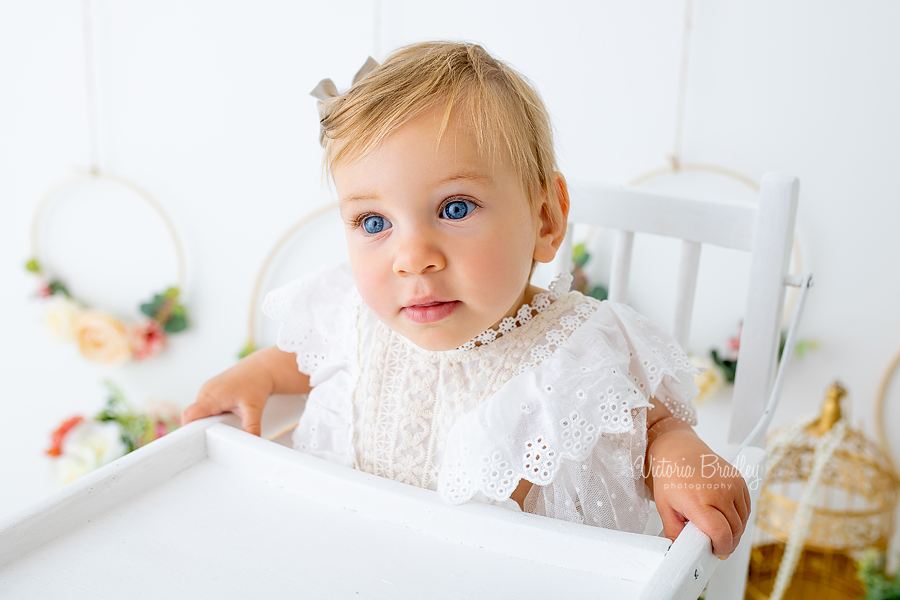 floral cake smash baby in white high chair