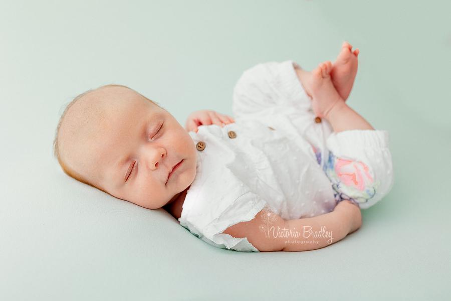 baby girl newborn on green backdrop